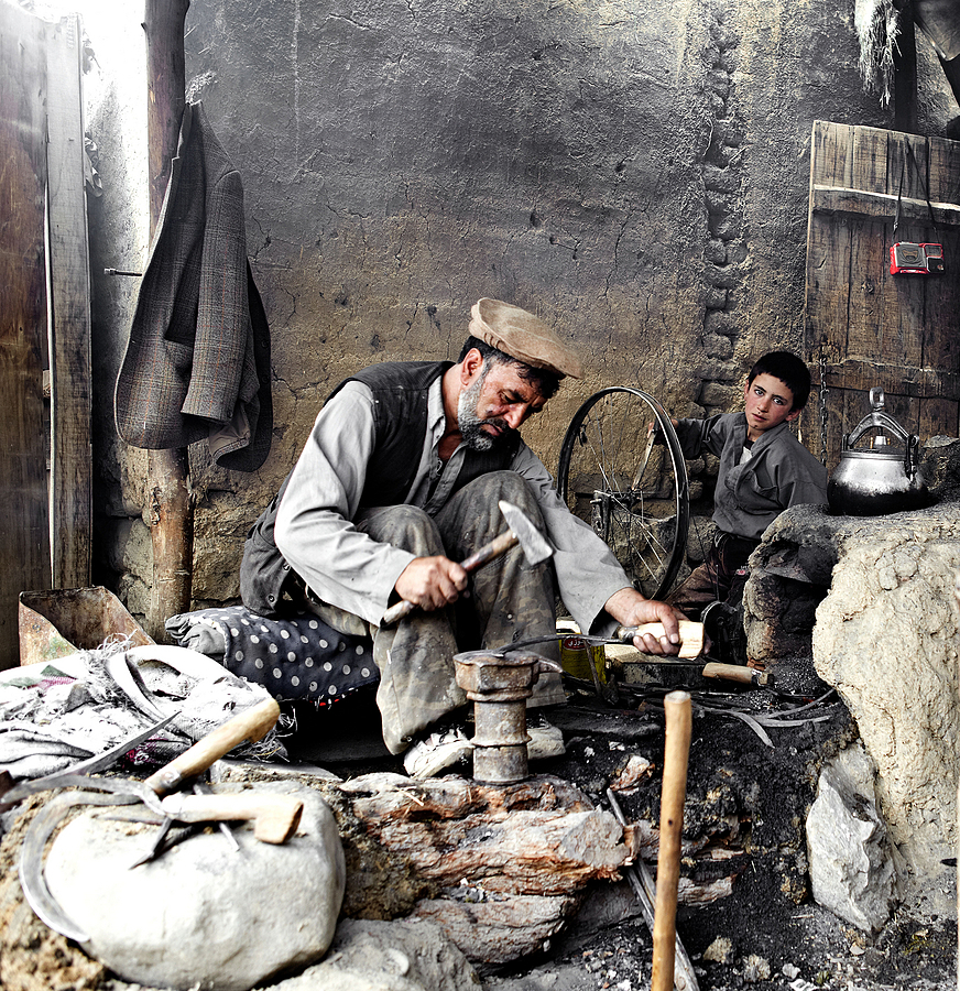 Blacksmith works the metal whilst son turns the wheel to keep the furnace burning Kabul | SUMMILUX-M 1:1.4/50 ASPH <br> Click image for more details, Click <b>X</b> on top right of image to close